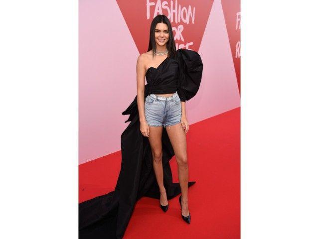 Cannes 2017: Kendall Jenner lancia una nuova tendenza per lo strascico. Dopo il mini abito di Giambattista Valli indossato per il red carpet di sabato, per l'evento di Fashion For Relief indossa shorts di jeans e maglia monospalla in velluto arricchita da strascico extra lungo, tutto Yves Saint Laurent.