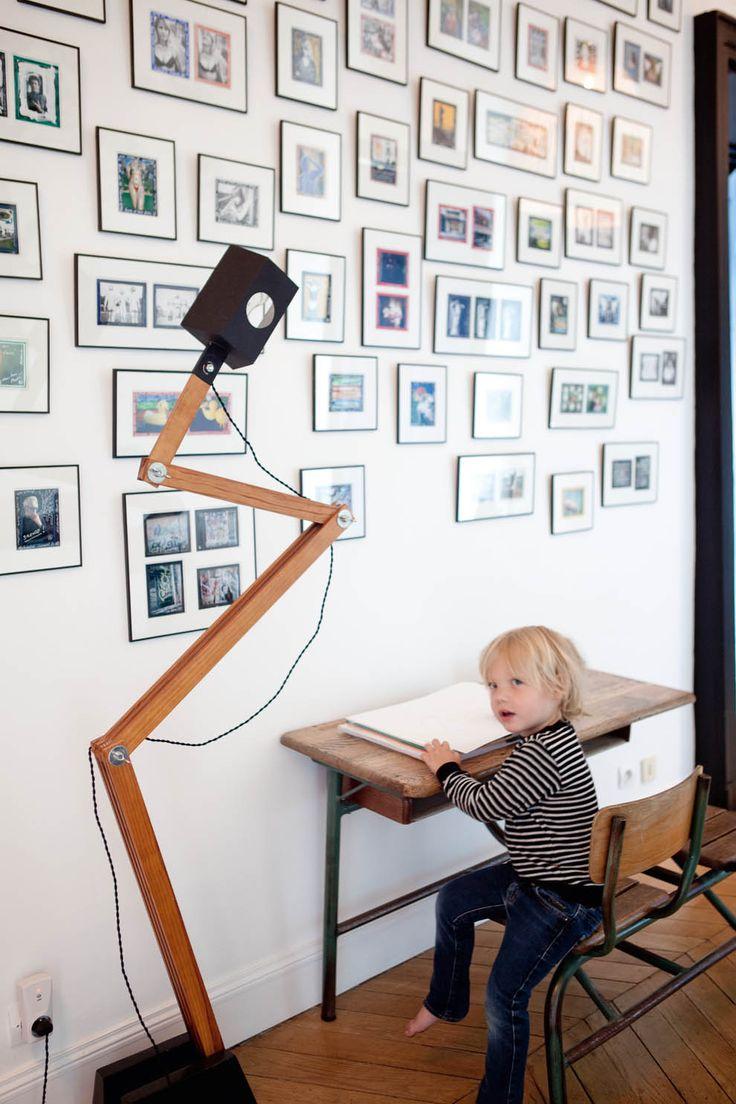 Mur de photos chez Sarah Lavoine : photos diverses posées sur un fond de couleur qui réhausse les teintes dominantes de l'image, de formats et de sens différents et encadrées sobrement sur un fond blanc avec une baguette noire