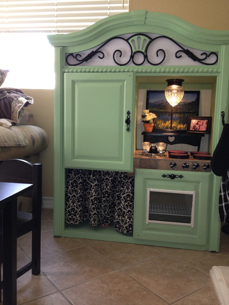 Play kitchen for toddlers made from an entertainment center.
