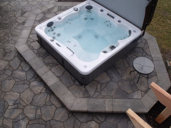 Sunken hottub surrounded by paving stone.