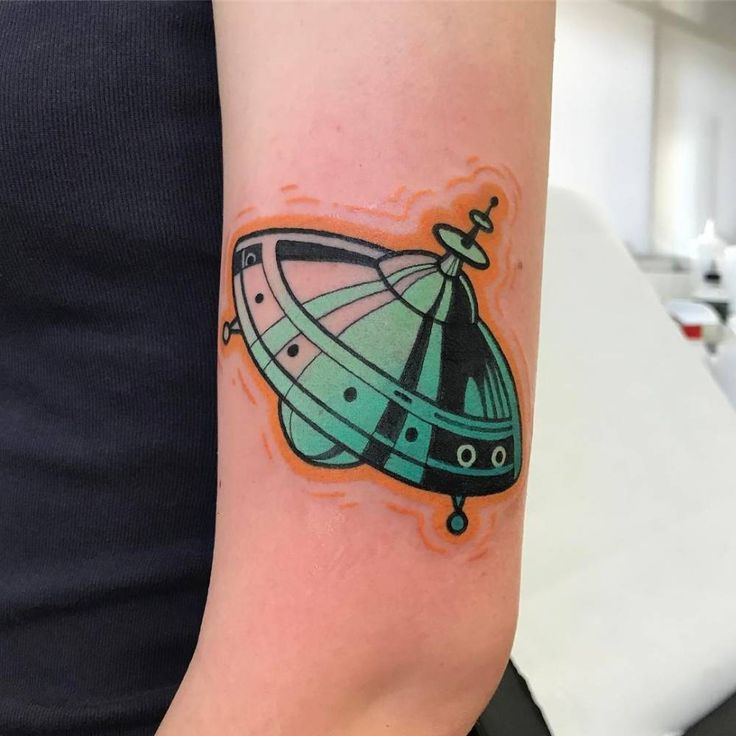 UFO tattoo on the left upper arm.