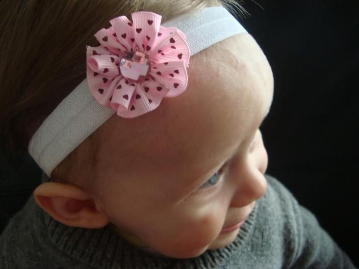 Skinny (1/2 inch) stretchy comfortable elastic headband (white) with super sweet fabric flower with a faux gem in the middle. Flower measures about 4