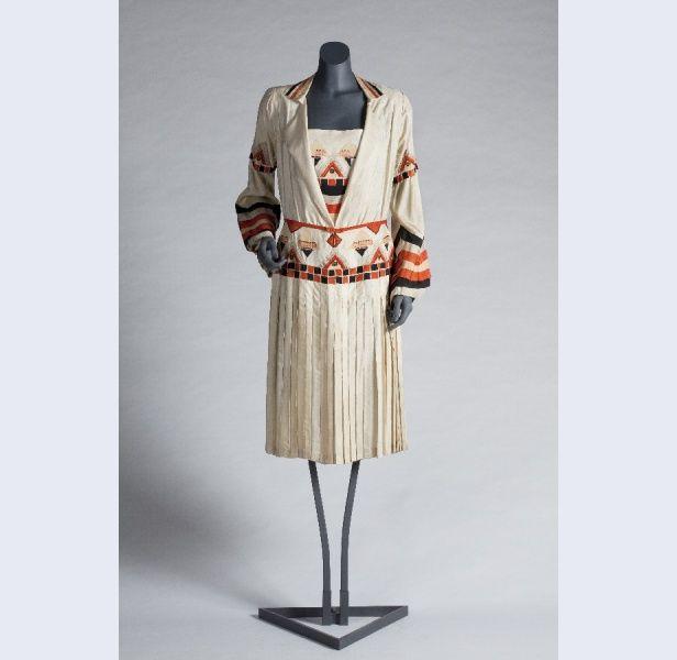 Metz & Co (modehuis) Jurk met losse modestie van naturelkleurige shantung met applicaties van zwarte zijde, abrikooskleurige zijde en oranje...