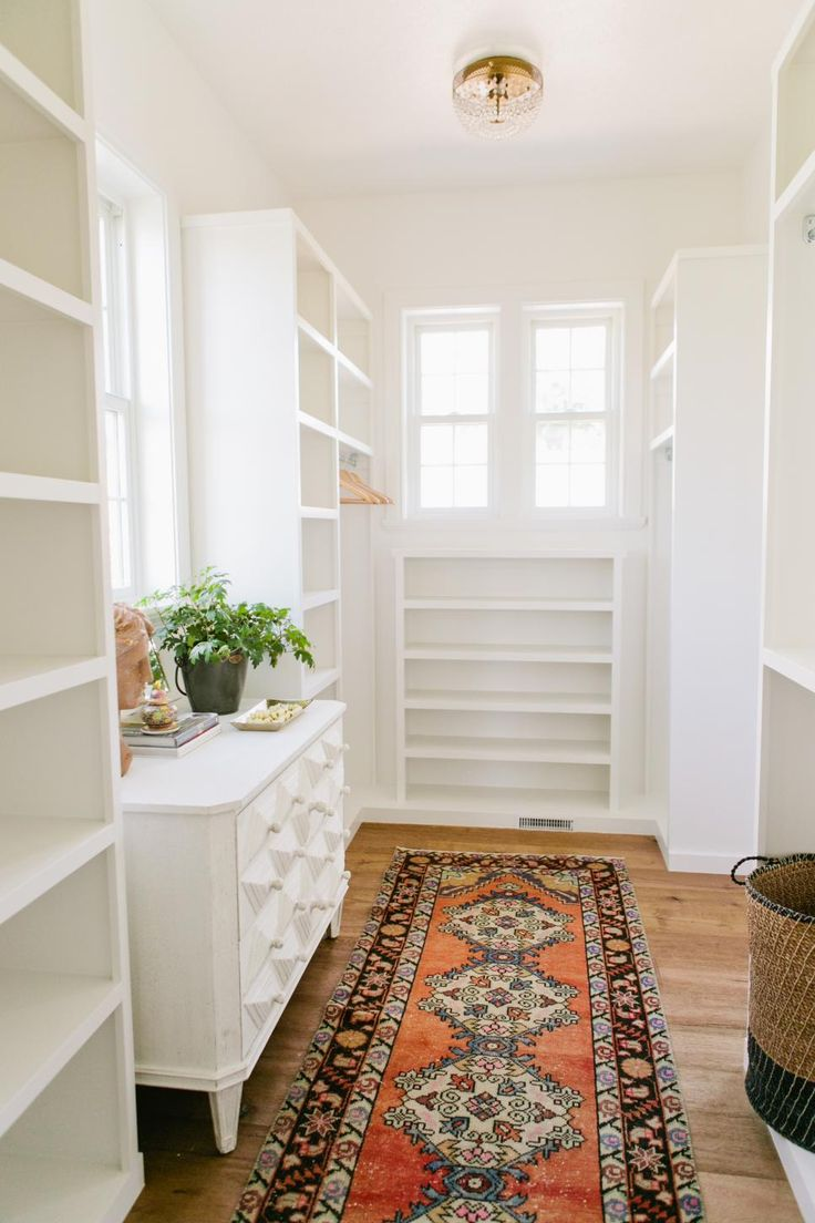 Built in white shelves provide ample space to organize clothes  shoes and accessories in this master walk in closet  A small white dresser with several