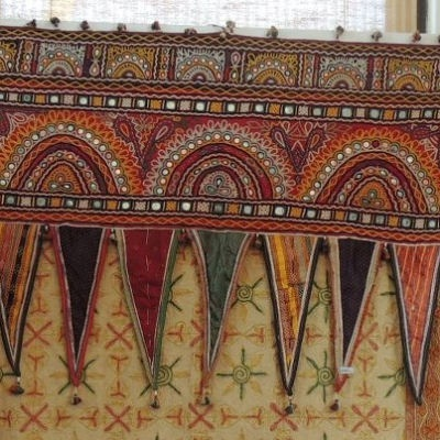 Toran may also refer to a decorative door hanging in Hinduism, usually decorated with marigolds and mango leaves, or a string that is tied on the door with the flower on it as a part of traditional Hindu culture on the occasion of festivals and weddings. A toran may feature colours such as green, yellow and red. They can be made of fabrics or metals which are usually made to resemble mango leaves.
