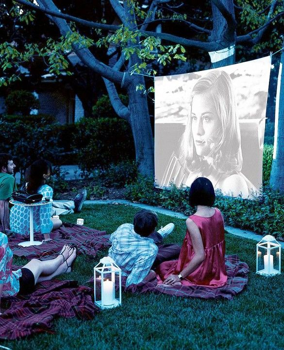 Outdoor movie with lawn seating on blankets and lantern lighting.