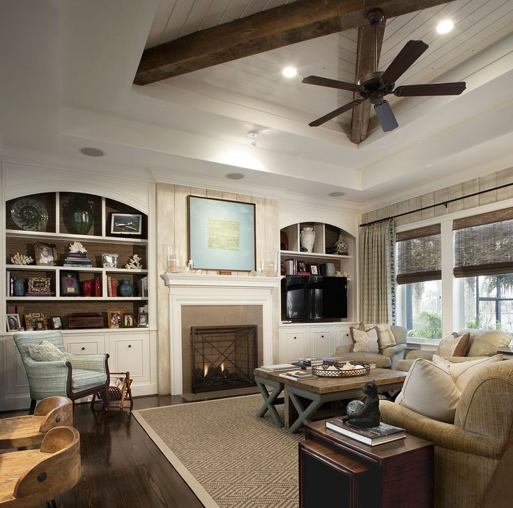 Neutral Living Room With Beamed Ceiling Hardwood Floors White Built Ins Flanking The