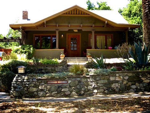 Craftsman Bungalow: Love the wood shingles, earth tone paints, door and window trim, exposed rafter tails, mission style lantern light, nice landscaping, centered stairs onto enclosed porches, and interesting windows. Not crazy about the stone shape/texture in the wall.