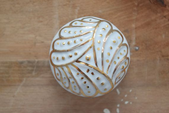 This white ceramic drawer knob has a textured design with painted gold highlights. Details ====== Length: 2 1/2 Projection: 1 3/8 Maximum thickness