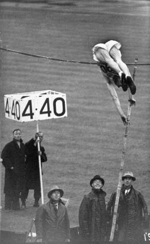 """1948 London Olympics: Caption from LIFE. """"Guinn Smith of U.S. won the hard way -- in a driving rain which caused vaulters' hands to slip from bamboo poles and made Olympic record impossible. Above, Smith's body is draped over bar as he fails on first try at winning height. Next time he made it.""""  Photos From LIFE Magazine - LIFE"""