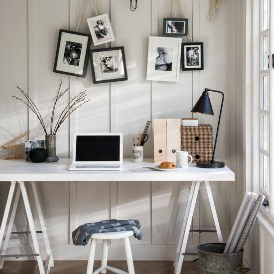 White desk in front of white panelled wall with black picture frames