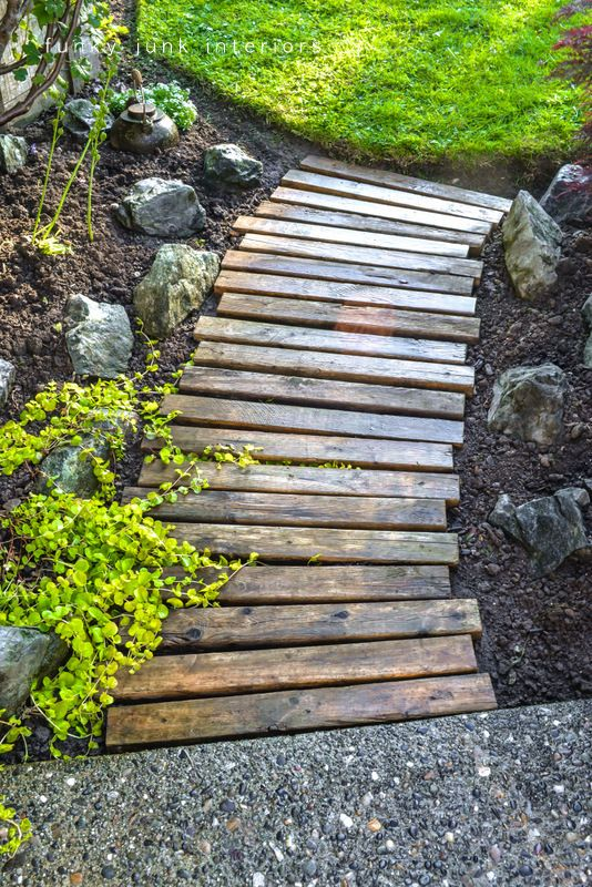Creating a pallet wood garden walkway is easy and cheap! The secret to this walkway is using pallet or crate boards with a little more depth for water run off. via funkyjunkinteriors.net