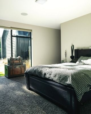 The master bedroom has a neutral colour palette accented with dark timber and SmartStrand carpet; there are no curtains, ...