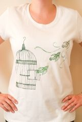 A graphic of a bird flying free from its cage is printed on this 100% fair trade, organic cotton T-shirt is made by the women of Freeset in Kolkata, India. The back features a small Stop Traffick Fashion logo near the neckline. When selecting your size please note that this is a slim fitting shirt. Freeset is a fair trade business offering employment to women trapped in Kolkata's sex trade. Click here to read more about the women helped by Freeset. $15.99