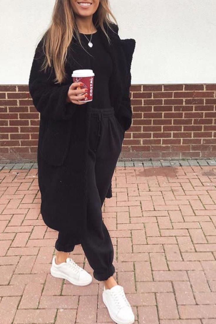 Modebewusste Frau hält sich bequem, lässig mit einem schwarzen Jog, einem langen schwarzen Mantel … – Outfits