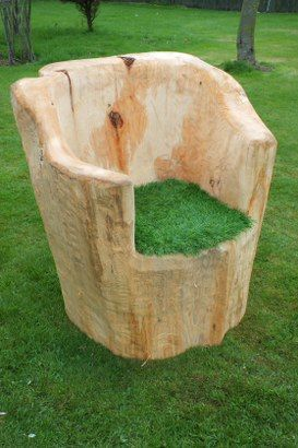 Chair chiseled out of a beautiful old log with some artificial grass for extra comfort