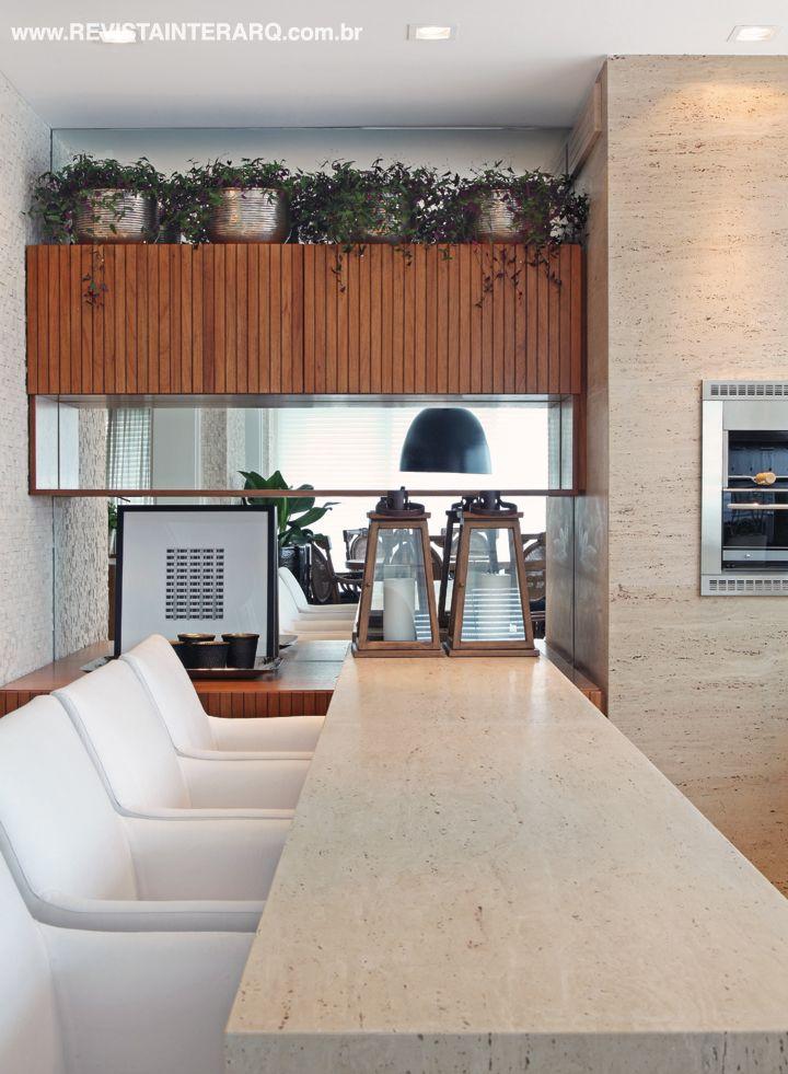 O mármore Travertino foi escolhido para a churrasqueira e bancada do espaço gourmet. O móvel sob medida ganhou espelhos para conferir fluidez e profundidade. Projeto de Ninha Chiozzini.