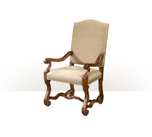 A hand carved mahogany armchair, the arched padded back and upholstered seat above scrolling hand carved legs joined by serpentine stretchers. Inspired by a Louis XIV original.