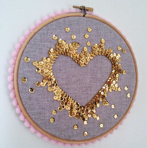 Handmade sequin art, each sequin has been sewn on individually to create a negative space heart. It is gold sequins on grey linen fabric, pale