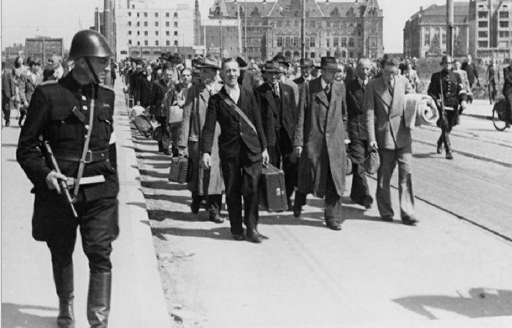 Een stoet NSB-ers op de Kruiskade, bewaakt door soldaten van de binnenlandsche strijdkrachten (BS), juni 1945. Op de achtergrond het stadhuis en het postkantoor aan de Coolsingel. De fotograaf is Van Langelaar en de foto komt uit het Stadsarchief Rotterdam.