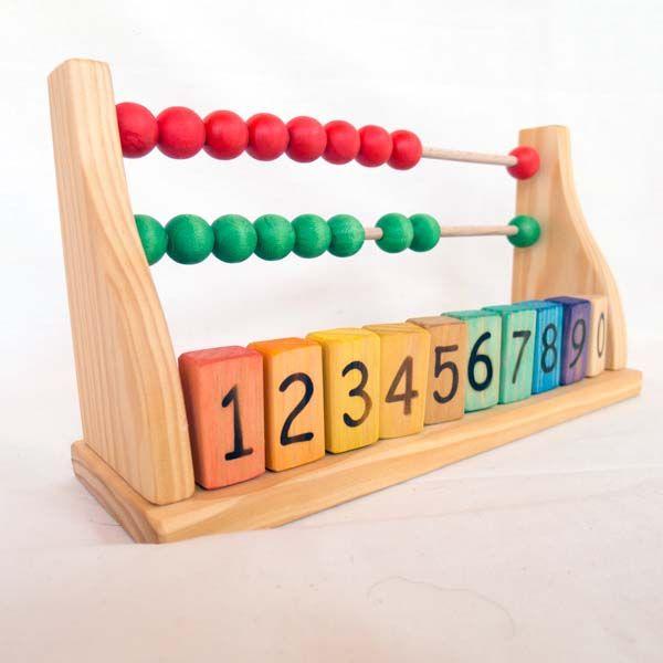 Con este ábaco de madera, que además incorpora números, los niños aprenderán a calcular mientras se divierten moviendo las cuentas de vivos colores de un lado a otro. Hecho a mano sin usar productos químico ni tóxicos y respetando el medioambiente. Juguete de madera basado en la pedagogía Waldorf.