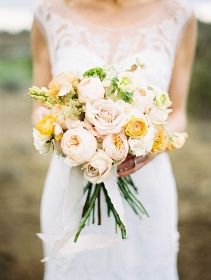 Naturally styled wedding bouquet with blush roses and hints of yellow.