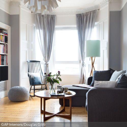 Der runde Couchtisch aus Holz komplettiert diese gemütliche Sitzecke. Ein schwarzer Schaukelstuhl, der graue Sitzpouf und das Ecksofa schaffen ausreichend Gelegenheit…