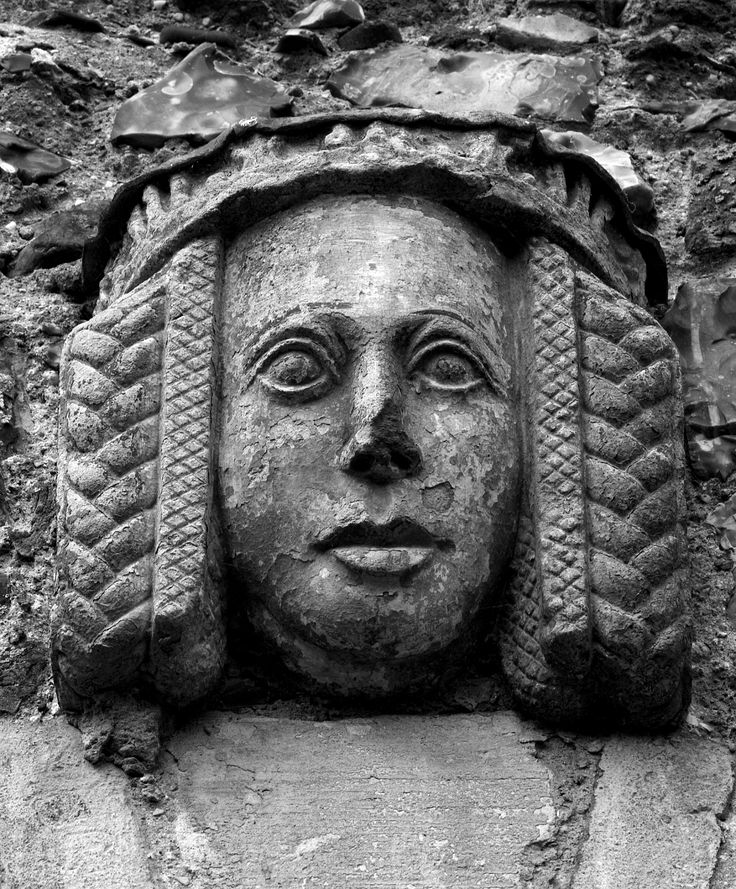 """probably 14th century England  """"One of the Medieval Heads above the windows on the poorhouse at Framlingham Castle."""" Obvious padding between the face and the braids.  Appears to be an embellished strip of something laying overtop the padding.  Also, the padding seems to either be embellished itself, or possibly have a netting of some kind over top of it."""