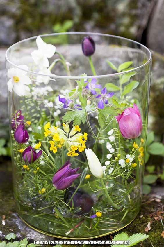 """Lovely spring or Easter """"terrarium."""" Spring flowers in a tall and wide glass vase."""