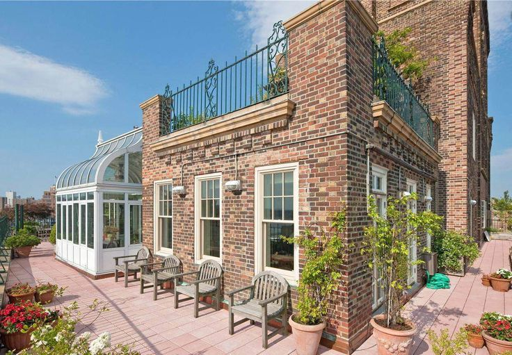 patio deck with exposed brick, wood panneling, plants and wood outdoor chairs