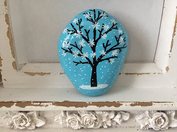 DETAILS: This miniature scene depicts a silhouette tree against a turquoise sky during a magical snow fall. Its hand-painted on a river rock with acrylics and coated with a protective varnish. Since they are made with natural stones, they vary in shape and size. They measure anywhere