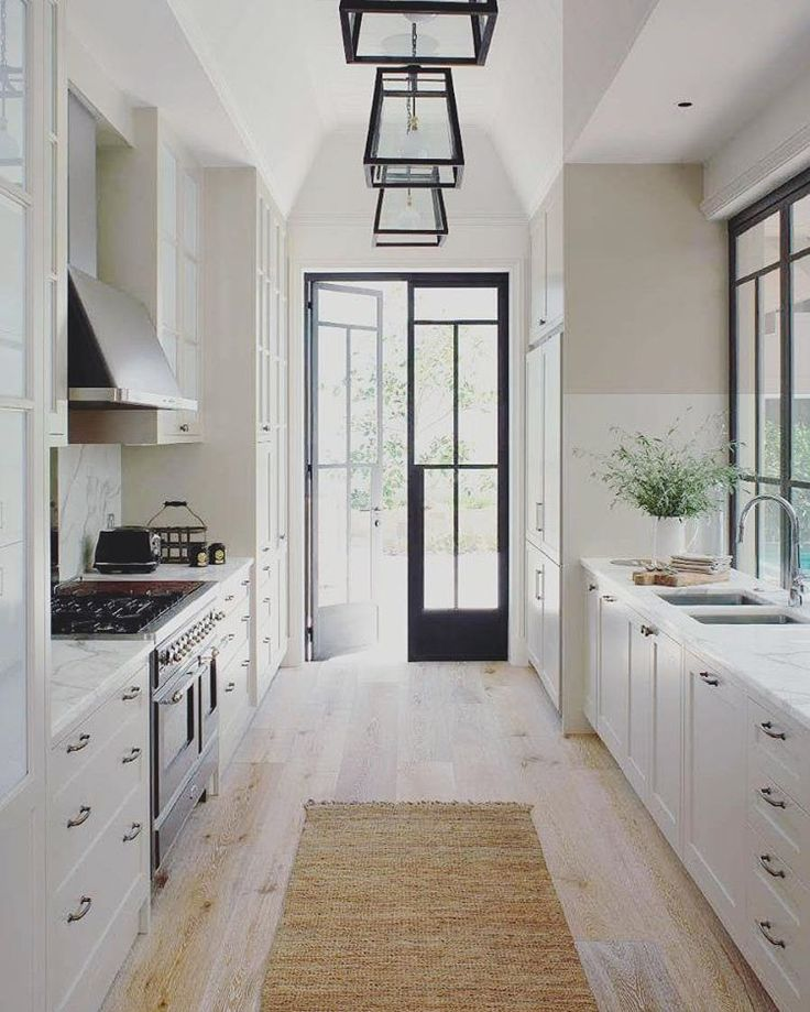 amazing galley kitchen with wide plank floors jute runner and blackframed french doors to the outside