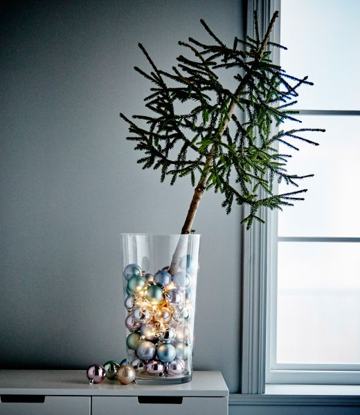 Interiérová dizajnérka sedí na podlahe a tvorí dekorácie na vianočný stromček.