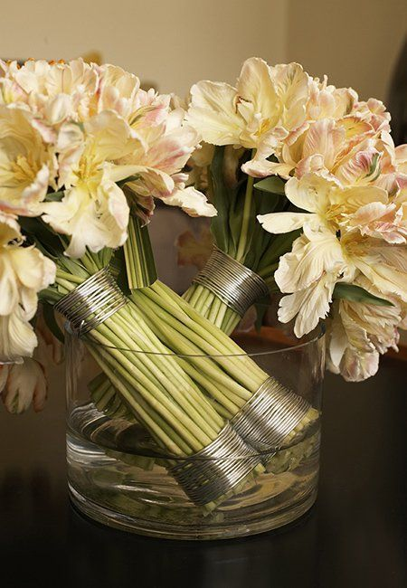 This arrangement features three bouquets of parrot tulips wrapped with aluminum wire.