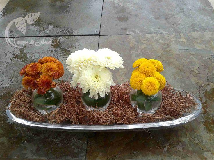 Crisantemos sobre ramas naturales en mini-floreros y plato de vidrio.