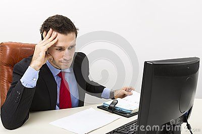Concentrated business man in his office with right hand on his head.