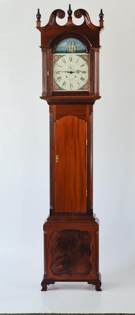 Tall Clock - by Jerome Olson.  This 18th century tall case clock is based on Jeff Headley's design using Mahogany with Mahogany crotch veneer in the inset panel and white pine secondary wood. The clock works were supplied by Green Lake Clock and the dial was painted by Dial House2.The finish is multiple sprayed coats of blonde shellac mixed from shellac flakes.