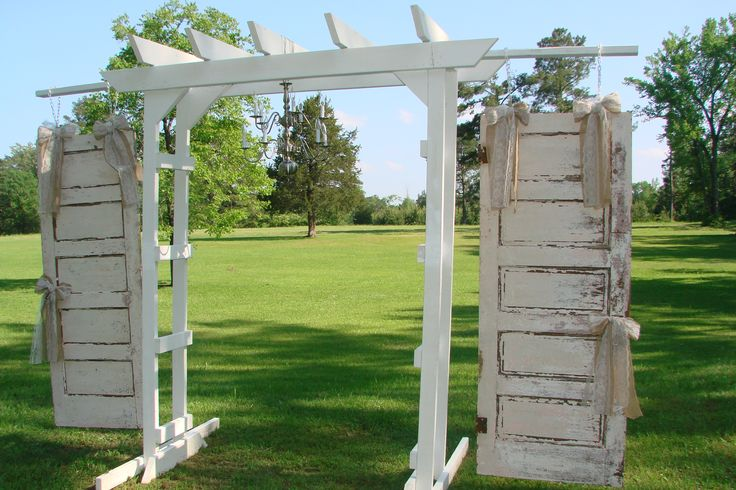 Double arch adorned with vintage white doors creates a