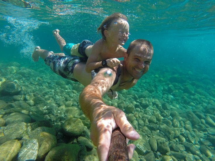 """Photo of Jared Eygabroad with son Cash who wrote, """"We always go swimming in the Chelan River because we have it all to ourselves.  We try to find secret swimming holes, avoiding the thousands of tourists that crowd the nearby lake's beaches each summer.  This photo was taken in our favorite secret swimming hole""""."""