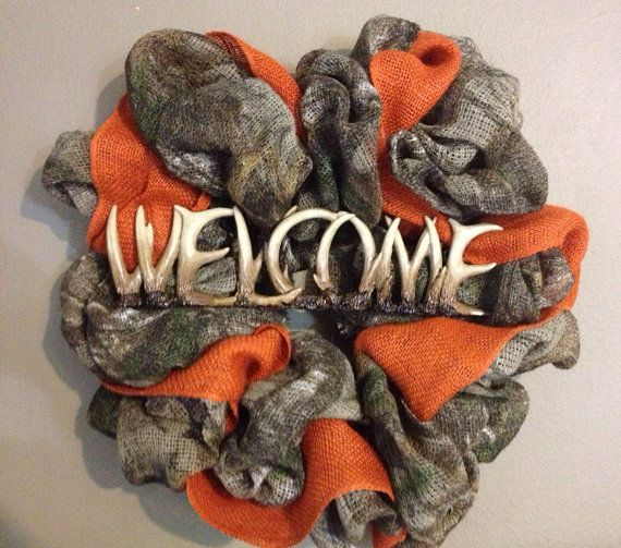 Camo and orange burlap wreath with deer horn welcome plaque on Etsy, $55.00
