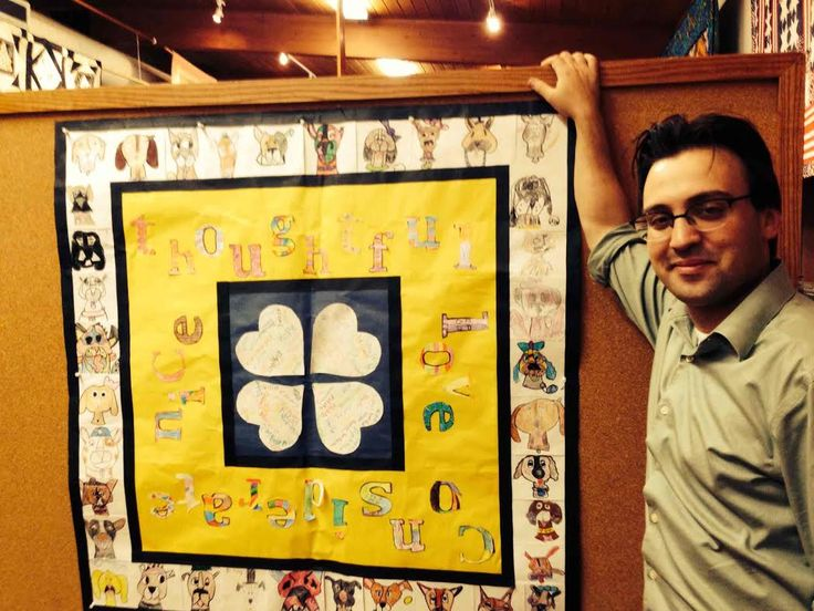 Curator Ben Justman with the paper version of the CritterKin Kindness Quilt.