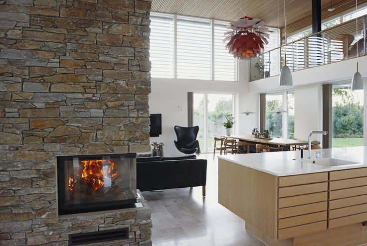 Fireplace build into the wall centeret next to the open kitchen. The kitchen is made by Multiform.