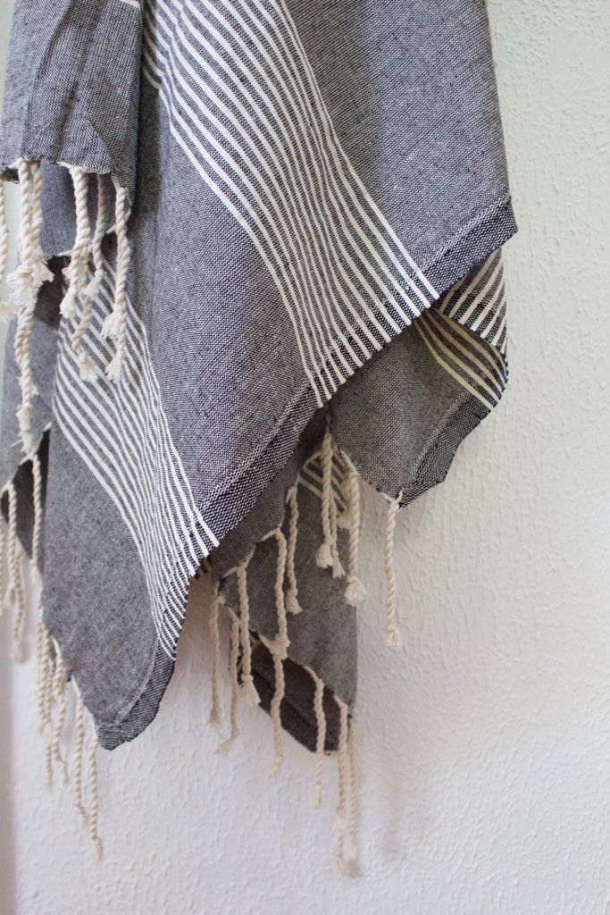Cotton turkish bath towel in charcoal black with tasseled ends.