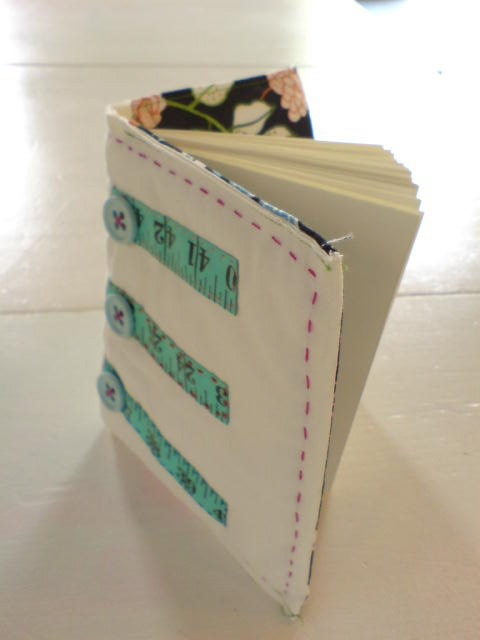 Fabric coverd book with measuring tape and buttons