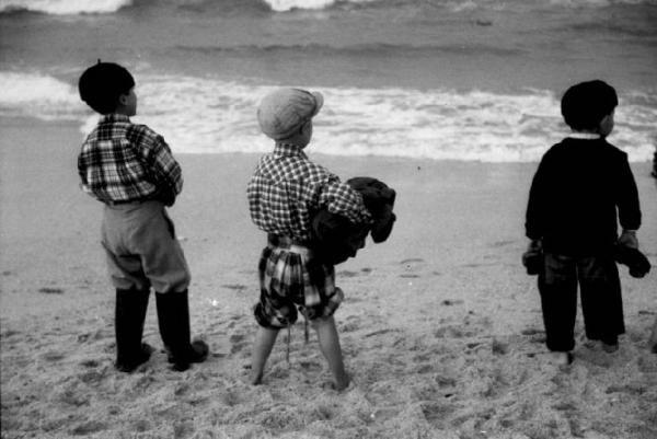 Spiaggia di Nazareth - bambini osservano il mare e le barche da pesca al rientro., Patellani, Federico – Fotografie – Lombardia Beni Culturali