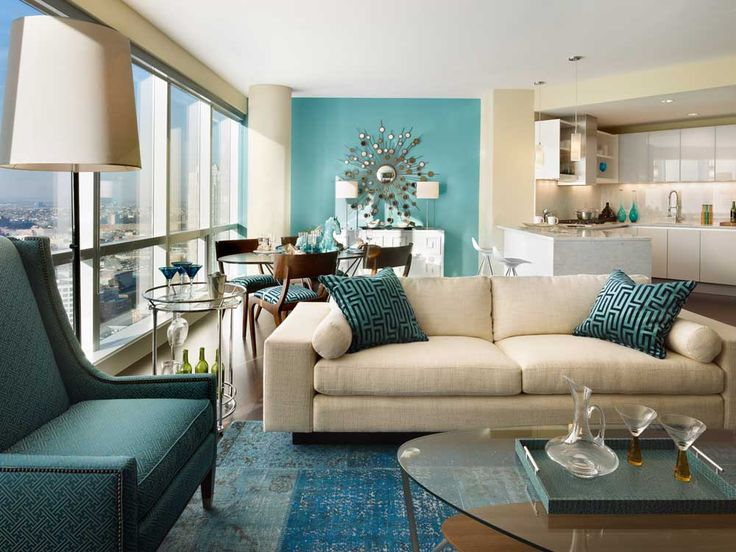 Teal Lounge Design with blue rug brown sofa blue high armchair glass tables big pendant light wide glass windows blue brown wall painting