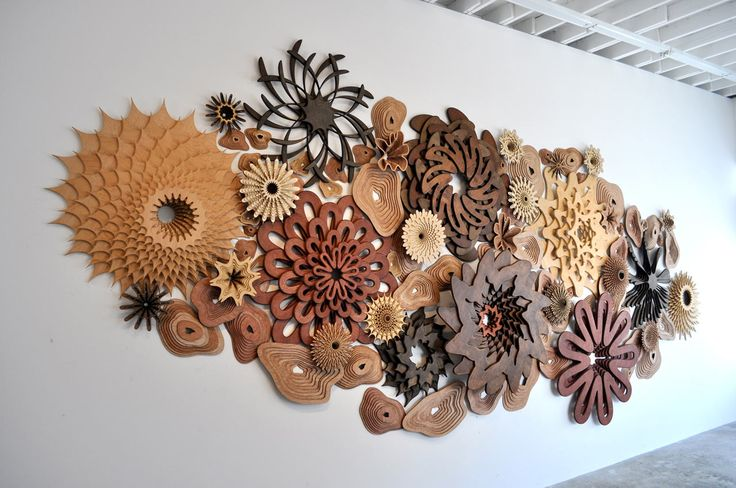 Artist Joshua Abarbanel.  The three-dimensional sculptures are made up of cut wooden forms that are meticulously laid out and layered to form reef-like compositions of complex marine wonderlands. The elements are stained in various tones creating depth just like you'll see on the ocean floor.