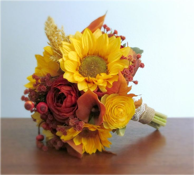 Silk and real touch flower bridal bouquet with orange and yellow ranunculus, orange calla lilies, sunflowers, fall leaves, gypsophila (baby's breath) berries, wheat, and pine cones. #fallwedding #autumnwedding #PosiesPearls