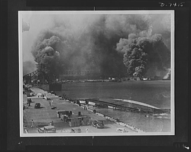 Pearl Harbor bombing. Destruction. Smoke pours from the USS Shaw, bombed dry dock (right center) while in the foreground lies the capsized USS Oglala, a minelayer. To the left is the 10,000 ton cruiser, USS Helena, struck by an aerial torpedo on the starboard side. The concussion caused the Oglala, formerly berthed alongside the Helena to flood and she turned over after being brought to dock. At the extreme left, may be seen some of the superstructure of the USS Pennsylvania and at the right…