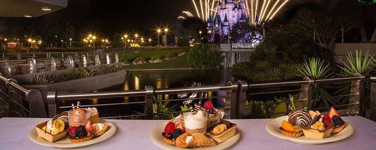 Fireworks and Desserts at Disney World Magic Kingdom- A plated variety of desserts outdoors at Tomorrowland Terrace Restaurant overlooking the water with a view of the fireworks by Cinderella Castle